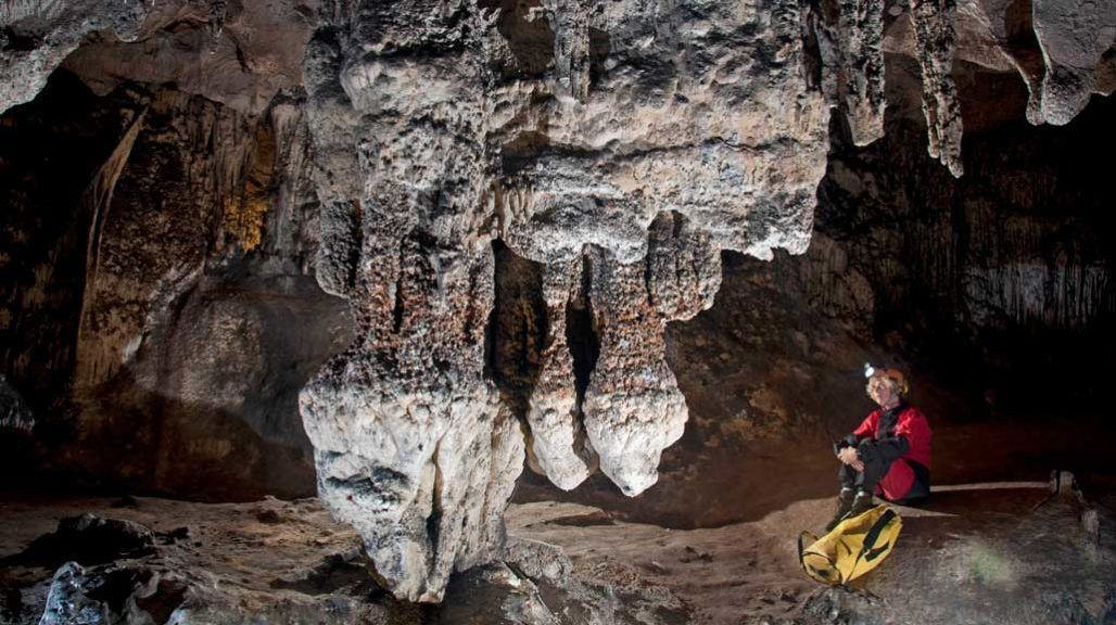 Featured image of cave structures described in story, with a geologist alongside.